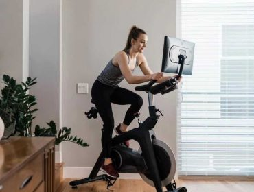 a woman rides a Stryde exercise bike for the DynasysTech review