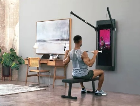 a man does strength training on the Tonal